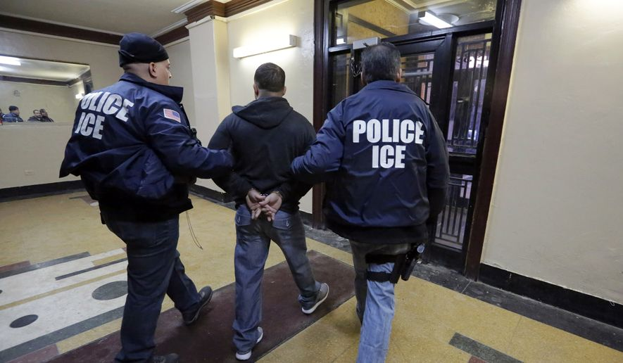 Immigration and Customs Enforcement officers escort an arrestee during a series of early-morning raids on March 3, 2015, in the Bronx borough of New York. (Associated Press) ** FILE **