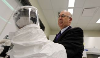 In this May 5, 2016 photo, Dr. Stephen Higgs, Director of Biosecurity Research Institute at Kansas State University in Manhattan, KS., holds hazmat gear. Higgs says a person will get bitten by a mosquito jn the United States that carries the Zika virus. (AP Photo/Josh Replogle)