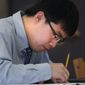 ADVANCE FOR USE SATURDAY, MAY 21, 2016, AND THEREAFTER- In this May 9, 2016, photo, Simon Zhang works on a test during one of his classes in Hyannis, Mass. Zhang is a senior who is in his second year at Pope John Paul and is one of four elected members of student council. (Steve Haines/The Cape Cod Times via AP)  MANDATORY CREDIT; MAGS OUT; NO SALES; TV OUT