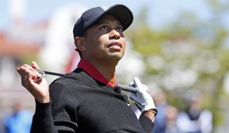 Tiger Woods watches a hit before hitting three ceremonial golf balls during a Quicken Loans National tournament media availability on the 10th tee at Congressional Country Club, Monday, May 16, 2016 in Bethesda, Md. (AP Photo/Alex Brandon)