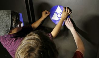 Destin Cramer, left, and Noah Rice place a new sticker on the door at the ceremonial opening of a gender neutral bathroom at Nathan Hale high school Tuesday, May 17, 2016, in Seattle. President Obama's directive ordering schools to accommodate transgender students has been controversial in some places but since 2012 Seattle has mandated that transgender students be able to use of the bathrooms and locker rooms of their choice. Nearly half of the district's 15 high schools already have gender neutral bathrooms and one high school has had a transgender bathroom for 20 years. (AP Photo/Elaine Thompson)
