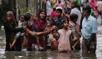 Sri Lankans wade through a road submerged in flood waters in Colombo, Sri Lanka, Tuesday, May 17, 2016. The Disaster Management Center said that 114 homes have been destroyed and more than 137,000 people have been evacuated to safe locations as heavy rains continue. (AP Photo/Eranga Jayawardena)