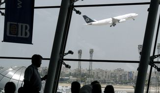 Western tourists stand watching an EgyptAir plane as it takes off at Cairo International Airport on June 4, 2008. (Associated Press) ** FILE **