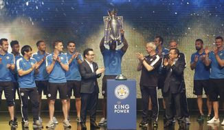 Leicester City captain Wes Morgan, center, holds the trophy of English Premier League soccer champions to celebrate with his teammates, Leicester City Chairman Vichai Srivaddhanaprabha, foreground right, Leicester City Manager Claudio Ranieri, center foreground second right, and Leicester City Vice Chairman Aiyawatt Srivaddhanaprabha, center left, during a press conference in Bangkok, Thailand, Wednesday, May 18, 2016. English Premier League champions Leicester City arrived in Bangkok to present their trophy to the Thai people. Leicester is owned by Thai duty free group King Power, run by Chairman and CEO Vichai Srivaddhanaprabha. (AP Photo/Sakchai Lalit)
