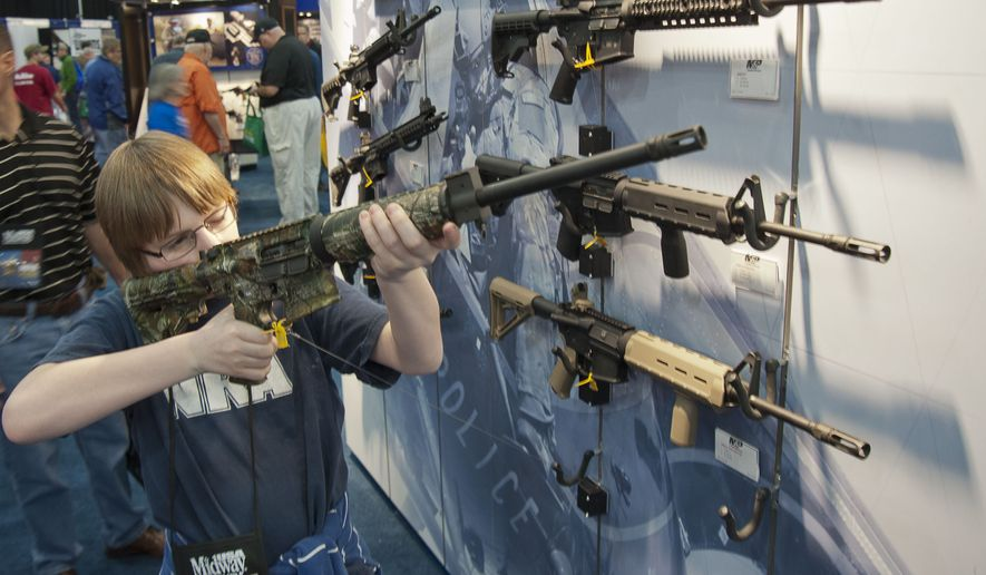 A young man who chose not to give his name sizes up an assault-style rifle during the National Rifle Association's annual convention on May 3, 2013, in Houston. (Associated Press)