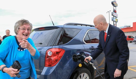 Nebraska Gov. Pete Ricketts pumps E-85 ethanol blend fuel into a car whose driver reacts to the presence of photographers, while visiting the Sapp Brothers Travel Center in Omaha, Neb., Thursday, May 19, 2016, to promote renewable fuels month in Nebraska. (AP Photo/Nati Harnik) ** FILE **