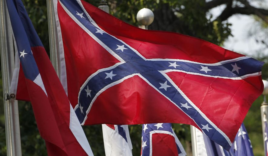 FILE - In this July 19, 2011 file photo, Confederate battle flags fly in Mountain Creek, Ala. The House has voted to ban the display of the Confederate flag on flagpoles at Veterans Administration cemeteries. The 265-159 vote would block descendants and others seeking to commemorate veterans of the Confederate States of America from flying the Confederate Battle Flag over mass graves, even on days that flag displays are permitted. (AP Photo/Dave Martin, File)