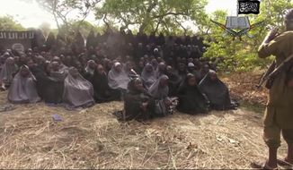 RETRANSMISSION TO REMOVE NAME OF POTENTIAL RAPE VICTIM - FILE - This May 12, 2014, file image taken from video posted by Nigeria's Boko Haram terrorist network purports to show the missing girls abducted from a boarding school in the northeastern town of Chibok. Soldiers have found one of the kidnapped girls, her uncle said Wednesday, May 18, 2016 describing her as pregnant and traumatized but otherwise fine. (Militant Video via AP, File)
