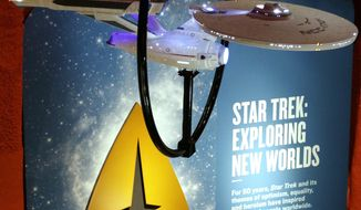 "In this photo taken Wednesday, May 18, 2016, a model of the USS Enterprise (NCC-1701) hangs above information about the exhibit, ""Star Trek: Exploring New Worlds,"" a 50th anniversary celebration of the ""Star Trek"" TV show and films at the EMP Museum, in Seattle. The exhibit opens Saturday. (AP Photo/Elaine Thompson)"