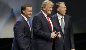 Republican presidential candidate Donald Trump is introduced by National Rifle Association executive director Chris W. Cox , left, and NRA executive vice president Wayne LaPierre as he takes the stage to speak at the NRA convention, Friday, May 20, 2016, in Louisville, Ky. (AP Photo/Mark Humphrey)