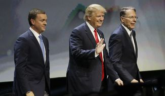 Republican presidential candidate Donald Trump is introduced by National Rifle Association executive director Chris W. Cox (left) and NRA executive vice president Wayne LaPierre as he takes the stage to speak at the NRA convention on May 20 in Louisville, Ky. (Associated Press)
