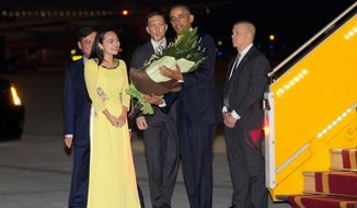 President Obama is given flowers by Linh Tran, the ceremonial flower girl, as he arrives Sunday at Noi Bai International Airport in Hanoi, Vietnam. (Associated Press)