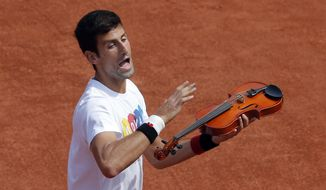 Serbia's Novak Djokovic joke with a violin before a training session of the French Open tennis tournament at the Roland Garros stadium, in Paris Saturday, May 21, 2016 . The French Open starts Sunday May 22. (AP Photo/Christophe Ena)