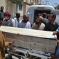 People stand near a coffin carrying a body one of the victims in a reportedly U.S. drone strike in the Ahmad Wal area in Baluchistan province of Pakistan, at a local hospital in Quetta, Pakistan, Sunday, May 22, 2016. A senior commander of the Afghan Taliban confirmed on Sunday that the extremist group's leader, Mullah Mohammad Akhtar Mansour, has been killed in the  strike. (AP Photo/Arshad Butt)