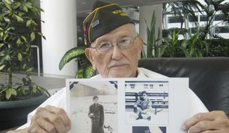 In this May 3, 2016, photo, Arthur Ishimoto, 93, a Japanese-American and U.S. Army Military Intelligence Service veteran, poses with archival photographs of himself as he is interviewed in Honolulu. (AP Photo/Audrey McAvoy)