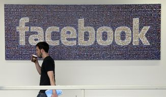 A Facebook employee walks past a sign at Facebook headquarters in Menlo Park, Calif. (Associated Press)