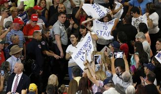 Protesters are removed during a speech by Republican presidential candidate Donald Trump at a campaign event in Albuquerque, N.M., Tuesday, May 24, 2016. (AP Photo/Brennan Linsley)