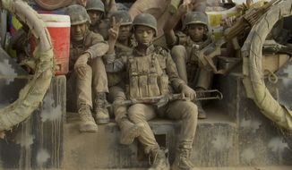 Iraqi federal police covered in dust arrive to join the forces surrounding Fallujah. (Associated Press)