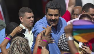 Venezuela's President Nicolas Maduro, shakes hands with supporters during a women's march for peace at Miraflores Presidential Palace in Caracas, Venezuela, Tuesday, May 24, 2016. Maduro is facing a movement by the opposition to force a referendum to recall him from office. (AP Photo/Ariana Cubillos) ** FILE **