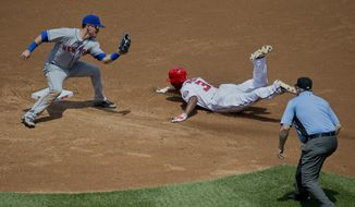 New York Mets shortstop Matt Reynolds, left, about to apply the tag on Washington Nationals Michael Taylor who attempted to steal second during the third inning of a baseball game at Nationals Park, Wednesday, May 25, 2016, in Washington. Calling the play is umpire Bill Welke. (AP Photo/Pablo Martinez Monsivais)