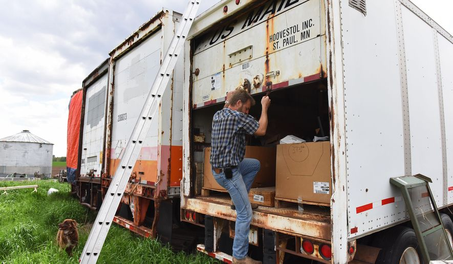 """ADVANCE FOR SUNDAY MAY 29 AND THEREAFTER - In a Thursday, May 19, 2016 photo, Mike DeVries stores parts in trailers on his farmstead outside of Alvord, Iowa. DeVries sells parts on eBay to customers around the world. DeVries wasn't sure what to make of the precipitous drop in sales on some items. When he checked the competition, he found 12-volt solenoids from China selling for $3.29 on eBay. Not only were prices lower, the items were offered with free shipping through an """"ePacket.""""  (Jay Pickthorn/Argus Leader via AP)"""