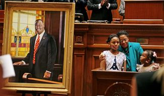 Jennifer Pinckney and daughters Eliana and Malana embrace after unveiling of the portrait of slain state Sen. Clementa Pinckney at the state Capitol, Wednesday, May 25, 2016, in Columbia, S.C. Clementa Pinckney died in that church along with eight others on June 17, leading a nighttime Bible study. Police said they were gunned down by a man motivated by racial hatred. (Gerry Melendez/The State via AP)