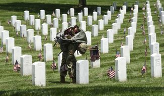 Members of the Old Guard place flags in front of every headstone at Arlington National Cemetery in Arlington, Va., Thursday, May 26, 2016. Soldiers were to place nearly a quarter of a million U.S. flags at the cemetery as part of a Memorial Day tradition. (AP Photo/Susan Walsh)