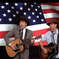 """Jimmy Fallon (l) and guest Adam Sandler (r) serenade the May 25, 2016 audience of """"The Tonight Show"""" with a tribute to U.S. servicemen entitled """"Friends On All Bases,"""" a parody of Garth Brooks's """"Friends In Low Places."""" Screen capture from a """"Tonight Show"""" YouTube video. Accessed May 26, 2016."""