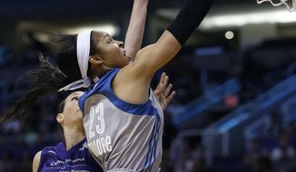 Minnesota Lynx's Maya Moore (23) drives past Phoenix Mercury's Sonja Petrovic (5) to score as Mercury's Mistie Bass, right, watches during the first half of a WNBA basketball game Wednesday, May 25, 2016, in Phoenix. The Lynx defeated the Mercury 85-78. (AP Photo/Ross D. Franklin)