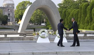U.S. President Barack Obam, right, and Japanese Prime Minister Shinzo Abe shake hands after laying wreaths at Hiroshima Peace Memorial Park in Hiroshima, western, Japan, Friday, May 27, 2016. Obama on Friday became the first sitting U.S. president to visit the site of the world's first atomic bomb attack, bringing global attention both to survivors and to his unfulfilled vision of a world without nuclear weapons. Atomic Bomb Dome is seen in the background. (AP Photo/Carolyn Kaster)