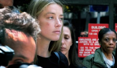 Actress Amber Heard leaves Los Angeles Superior Court court on Friday, May 27, 2016, after giving a sworn declaration that her husband Johnny Depp threw her cellphone at her during a fight Saturday, striking her cheek and eye. The judge ordered Depp to stay away from his estranged wife and ruled that Depp shouldn't try to contact Heard until a hearing is conducted on June 17. (AP Photo/Richard Vogel)