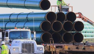 FILE - In this May 9, 2015, file photo, workers unload pipes for the proposed Dakota Access oil pipeline that would stretch from the Bakken oil fields in North Dakota to Illinois. The discovery of a possible American Indian burial site in northwest Iowa may require relocation of a crude oil pipeline route which would further delay the beginning of construction in Iowa, the only one of four states where work hasn't yet begun. The Dakota Access pipeline passes through the Big Sioux Wildlife Management area in Lyon County where an American Indian tribe said it has a burial site. (AP Photo/Nati Harnik, File)