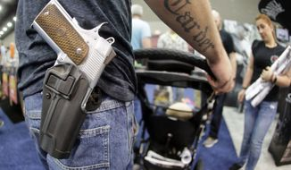 A man wears his handgun in a holster as he pushes his son in a stroller at the National Rifle Association Convention on May 21, 2016, in Louisville, Ky. (Associated Press)