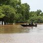 Two people pilot a boat through the flooded Brazos River on Sunday, May 29, 2016, in Rosenberg, Texas. (Jon Shapley/Houston Chronicle via AP) ** FILE **