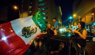 A woman waves the Mexican flag at the Albuquerque Convention Center after a rally by Republican presidential candidate Donald Trump in New Mexico. Analysts say anti-American sentiments and violence from protesters are chasing undecided voters toward the very man they are protesting. (Las Cruces Sun-News via Associated Press)