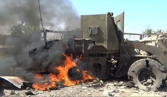 In this image posted on a photo sharing website by an Islamic State militant media arm on Monday, May 30, 2016, a military vehicle burns as ISIS fighters battle Iraqi forces and their allies west of Fallujah, Iraq. Iraqi forces battling their way into Fallujah repelled a four-hour attack by the Islamic State group in the city's south on Tuesday, a day after first moving into the southern edges of the militant-held city with the help of U.S.-led coalition airstrikes.(militant photo via AP)