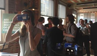 Guests look at 360-degree view of a Peace Corps village using Samsung technology goggles. Peace Corps officials said Wednesday they are making moves to refresh the image of the agency started by John F. Kennedy. The Peace Corps' in-house creative team collaborated with Ogilvy Washington to develop an updated look. (Jessie Fox/The Washington Times)