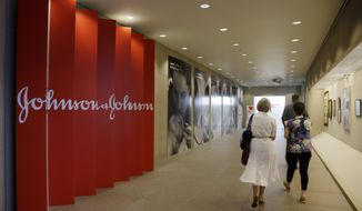 In this July 30, 2013, file photo, people walk along a corridor at the headquarters of Johnson & Johnson in New Brunswick, N.J. (AP Photo/Mel Evans, File)