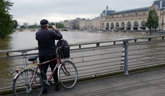 A cyclist photographs the flooding Seine river in front of the Musee d' Orsay in Paris, France Friday June 3, 2016. Both the Louvre and Orsay museums were closed as the Seine, which officials said was at its highest level in nearly 35 years, was expected to peak sometime later Friday. (AP Photo/Jerome Delay)