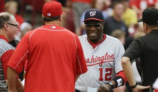 Washington Nationals manager Dusty Baker (12) shakes hands with Cincinnati Reds manager Bryan Price, center left, before a baseball game, Friday, June 3, 2016, in Cincinnati. (AP Photo/John Minchillo)