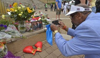 Frank Green, of Louisville, Ky., takes a photograph of a memorial for Muhammad Ali at the Muhammad Ali Center, Saturday, June 4, 2016 in Louisville Ky. Ali, the magnificent heavyweight champion whose fast fists and irrepressible personality transcended sports and captivated the world, has died according to a statement released by his family Friday, June 3.  He was 74. (AP Photo/Timothy D. Easley)