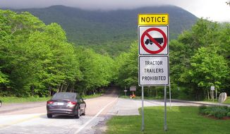 A sign warns truckers not to enter the Smugglers Notch portion of Vermont Route 108, known for its tight turns as it rises through a mountain pass, in Stowe, Vt., Friday June 3, 2016. (AP Photo/Wilson Ring) ** FILE **
