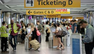 Travelers arrive at the departure terminal at LaGuardia Airport on May 27 in New York. (Associated Press)