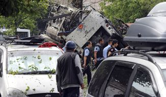 Turkish security officials and firefighters work at the explosion site after a bus carrying riot police official was struck by a bomb in Istanbul, Tuesday, June 7, 2016. At least five police officers were wounded. The blast occurred at a busy intersection near an Istanbul University building in the city's Beyazit district during the morning rush hour. (DHA via AP)