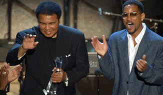 Actor Will Smith applauds as he presents the humanitarian award to boxing great Muhammad Ali during the 2nd annual BET Awards in Los Angeles on June 25, 2002. (Associated Press) **FILE**
