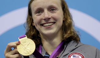 FILE - In this Aug. 3, 2012, file photo, United States' Katie Ledecky poses on the podium with her gold medal in the women's 800-meter freestyle swimming final at the Aquatics Centre in the Olympic Park during the 2012 Summer Olympics in London. Ledecky has been the world record holder in the 1,500-meter freestyle for almost three years, but the metric mile has never been part of the Olympic program for women. The longest event the 19-year-old can tackle at the Summer Games is the 800 free. (AP Photo/Michael Sohn, File)
