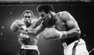 Muhammad Ali, right, winces as Ken Norton hits him with a left to the head in their scheduled 12-round re-match, Sept. 10, 1973 at the Forum in Inglewood, California. (AP Photo)