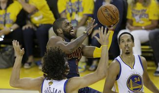 Cleveland Cavaliers guard Kyrie Irving, center, shoots against Golden State Warriors forward Anderson Varejao, bottom, and guard Shaun Livingston (34) during the second half of Game 1 of basketball's NBA Finals in Oakland, Calif., Thursday, June 2, 2016. (AP Photo/Marcio Jose Sanchez)
