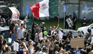 An anti-Donald Trump protester waves a Mexican flag outside the California Republican Party 2016 Convention on April 29 in Burlingame, Calif. (Associated Press)