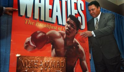 """In this Thursday Feb. 4, 1999, photo, Muhammad Ali, known as """"The Greatest,"""" poses next to a Wheaties poster during the unveiling of the 75th anniversary cereal box in his honor, in New York. Ali was one of the greatest athletes of all time, but he didn't cash in on product endorsements during his prime the way you'd expect today. Ali was featured on the Wheaties box in 1999, long after he retired, and was the first boxers to appear there. (AP Photo/Bebeto Matthews, File)"""